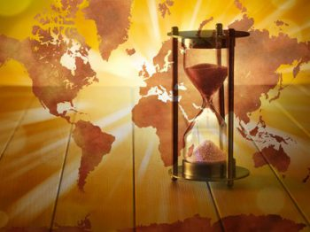 A conceptual image with an hourglass with a world map